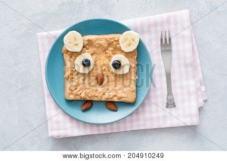 Peanut butter toast for kids healthy breakfast in shape of cute owl on a blue plate. Table top view