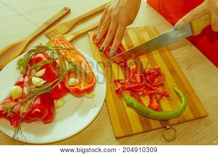 Young woman cooking healthy meal in the kitchen. Cooking healthy food at home. Woman in kitchen preparing vegetables - Retro color
