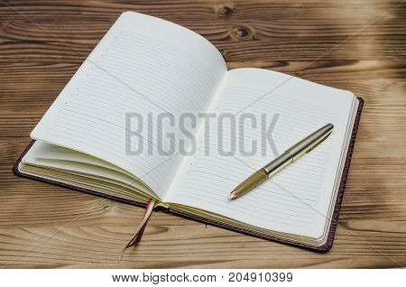 Open book with blank pages and fountain pen on wooden desk table. Education.
