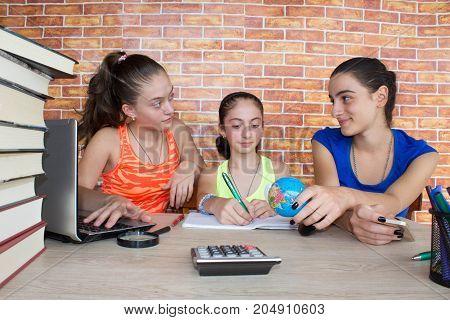 Three Girls work on his homework. Portrait of Three pretty girls high school student studying