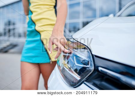 A young beautiful girl chooses a new car in the showroom. Buying a new car.