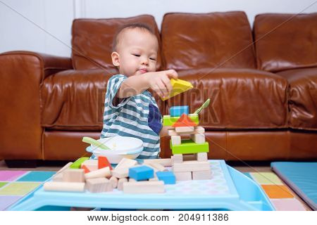 1 year old toddler baby boy child play with colorful wooden blocks. Kid playing with educational toys while eating snack in living room at home photo in real life interior