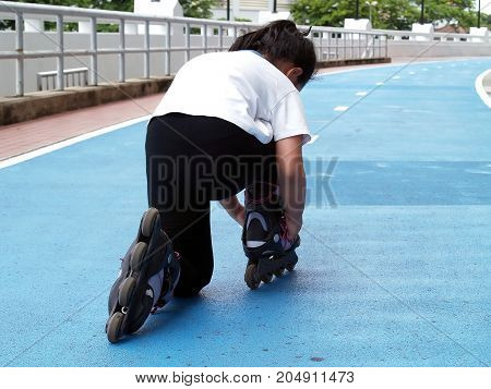 asian little girl kneel wearing roller skate shoes (inline skate or Rollerblade) on blue concrete racetrack in outdoor sports field