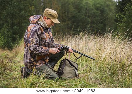 Hunter charges a hunting rifle with cartridges