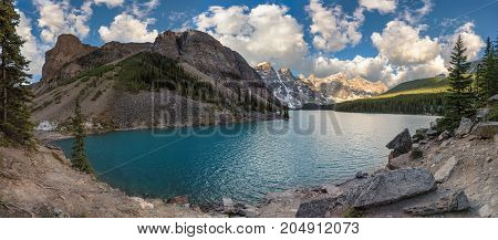 Panorama of Moraine Lake with snow-covered peaks above it in Banff National Park, Canadian Rockies, Alberta, Canada.