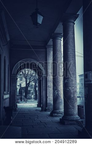 Old colonnade in the night. Architecture corridor