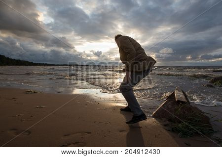 man alone on the seashore in the fall at sunset