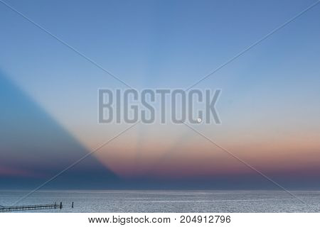 Abstract and dramatic sunset with light rays that create the shape of an inverted pyramid on the sea.