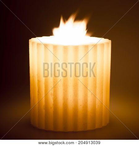 Isolated burning candle on dark background. Shallow DOF.