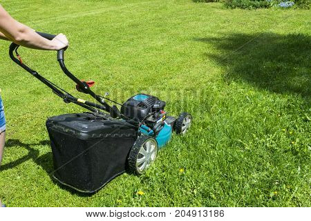 Beautiful girl cuts the lawn. Mowing lawns. Lawn mower on green grass. mower grass equipment. mowing gardener care work tool close up view sunny day