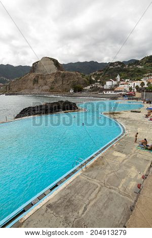 PORTO DA CRUZ MADEIRA PORTUGAL - SEPTEMBER 11 2016: People rest by the Swimming Pool in Porto da Cruz on Medeira. Portugal