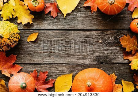 Fallen leaves and pumpkins on wooden background with copy space for text. Top view. Seasonal background for Halloween or Thanksgiving day
