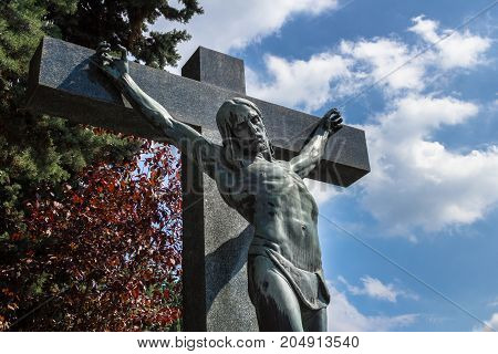 A statue of Jesus Christ crucified against dramatic sky. Jesus Christ on cross. Jesus christ statue in the cemetery.