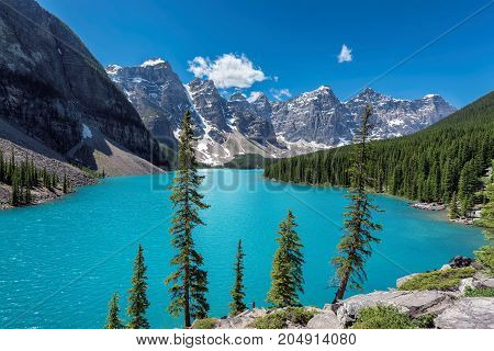 Beautiful turquoise waters of the Moraine lake with snow-covered peaks above it in Canadian Rockies.