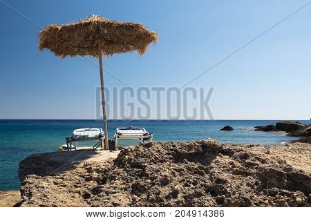 sunshade on the and two sun bed Mediterranean rocky beach