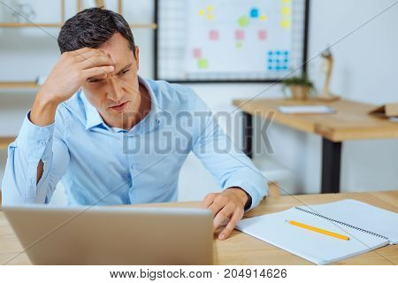 Want to concentrate. Angry man looking forward while touching his forehead and taking important decision