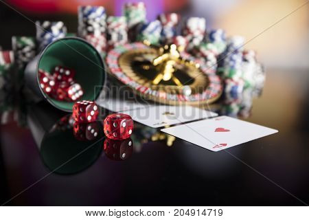 Casino thme. High contrast image of casino roulette, poker game, dice game, poker chips on a gaming table, all on colorful bokeh background.