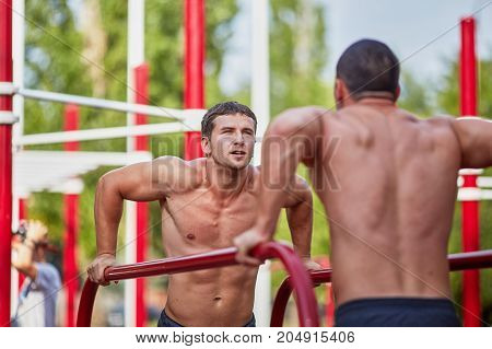 Healthy athletes are engaged on uneven bars on horizontal bar. Mans fitness with blue sky in the background and open space around him.