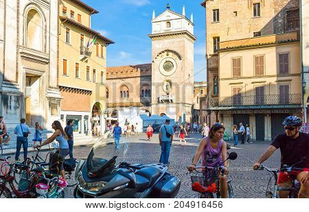 Mantova Italy - July 31 2011: Young people in Cathedral square with the Della Ragione tower in the background