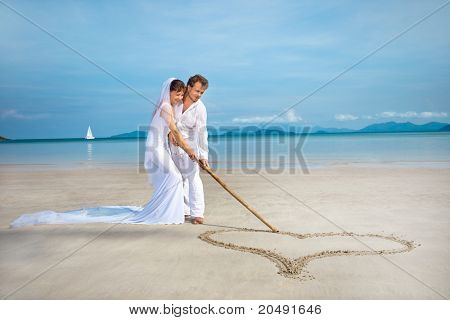 beautiful couple on the beach in wedding dress drawing heart