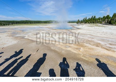 A group of visitors, represented by their shadows, looking at a large Geyser in the Norris Geyser Basin, Yellowstone National Park.