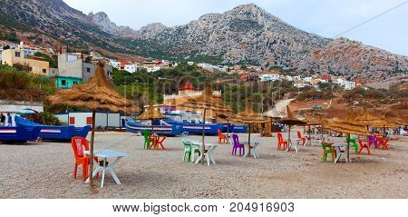Panorama of Beautiful coastline in morocco. belyouneche. Chairs And Umbrella In moroccan Beach. colorful chairs under umbrella at beach