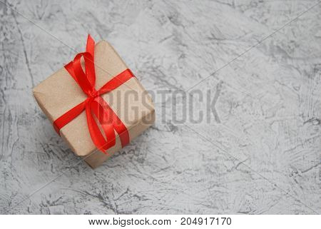 Rustic gift box craft paper and red bow on gray background