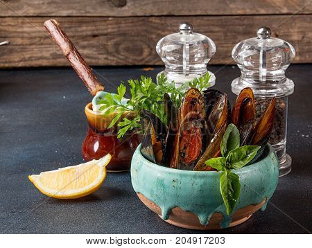 Mussels Baked With Butter And Parsley In Blue Ceramic Bowl Against Old Wooden Background.