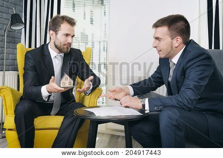 Real Estate Agent Discussing With Blueprints And House Model