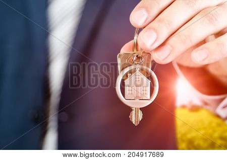 Real Estate Agent Holding Key Of New Apartment Close Up.