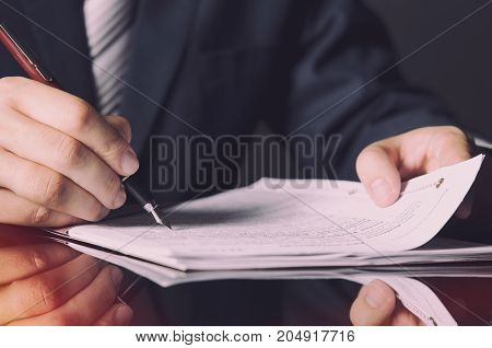 Notary Signing A Contract With Fountain Pen In Dark Room Concept