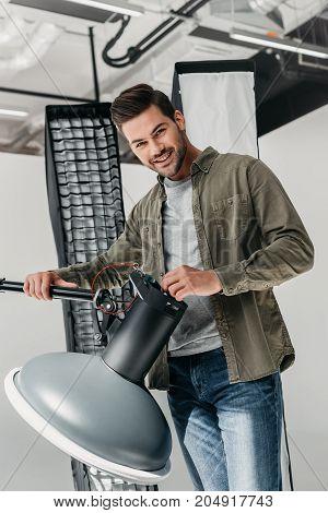 Photographer With Lighting Equipment In Studio
