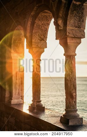 Old balcony with columns in Portovenere at sunset Italy.