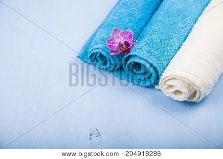 White And Blue Towels And An Orchid Flower.
