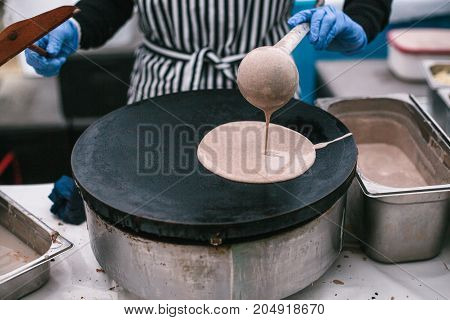 Cooking pancakes in the pan at the bakery. Own little business. The chef at work. Street food.