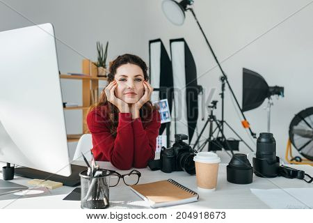 attractive female photographer with lenses photo camera and graphics tablet in modern office