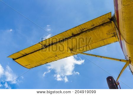 Vintage airplane seen from below with blue sky in the background