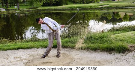 Businessman Golfer is in trouble and must find the solution to get out of the Sand Trap, Sport and Concept