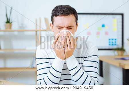 Crazy day. Frustrated office worker keeping eyes closed and holding hands together while cleaning nose