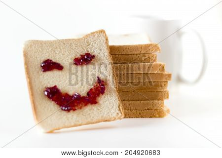 A smile at breakfast made of strawberry jam spread on a slice of bread.
