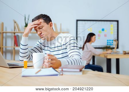 Cannot imagine. Ill office worker holding cup in left hand and closing eyes while putting hand on the forehead