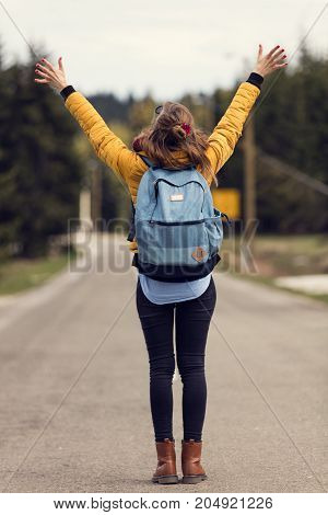 Girl walking down the empty road with arms wide open.