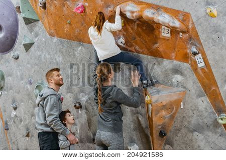 Little girl climbing a wall with grips and her mom supporting her from the back