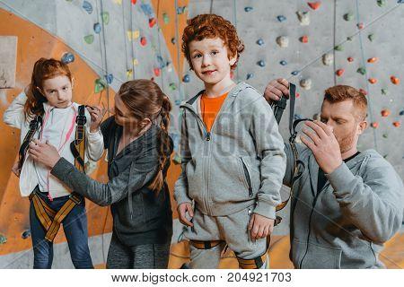 Parent Securing Children In Harnesses