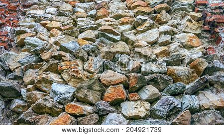 Stone old wall from huge blocks. Background of stones. The concept of reliability. The space between the stones filled with cement.