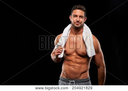 A handsome young sportsman standing half naked with a towel in his neck