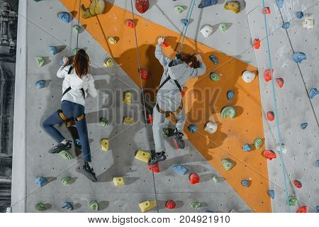 Two Little Kids Climbing Wall With Grips