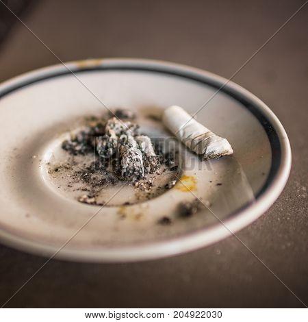 A saucer used as ashtrays. Shallow DOF.