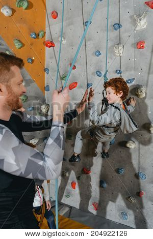 Boy On Climbing Wall High-fiving Father