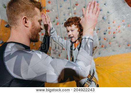Boy In Climbing Harness High-fiving Dad